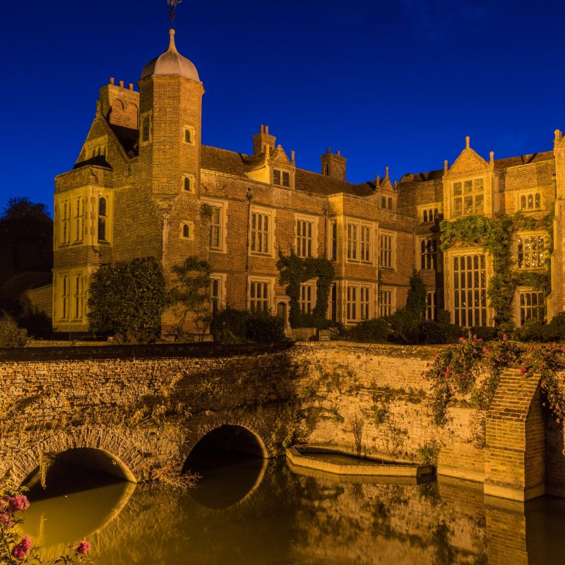 Kentwell Hall seen at floodlit at night with surrounding moat